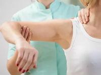 Врач осматривает плечо пациента