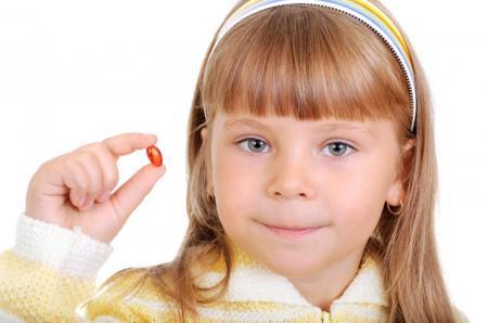 ребенок держит витамины