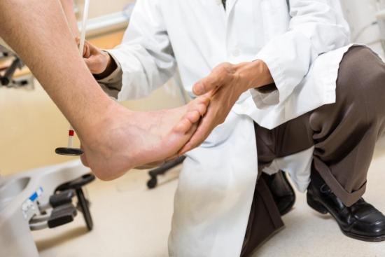 Врач осматривает стопу пациента